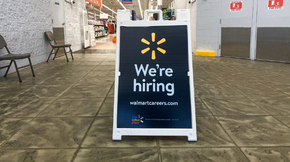 Sign at Walmart store entrance with brand logo and We're Hiring text-walmart hiring-ss-featured