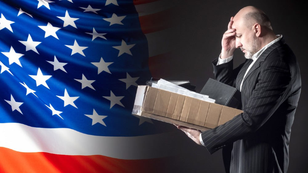 The dismissed employee clutched his head against the background of the US flag-Weekly Jobless Claims-ss-featured