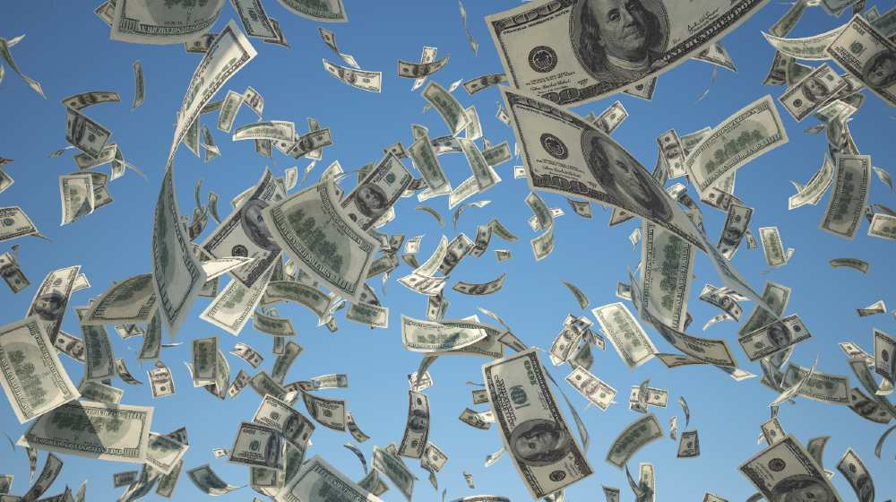 100 US Dollar, bills flying on blue sky background-ss-featured