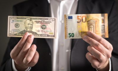Dollar vs euro. Business man in suit holding 50 banknote and bill in both currency in hand-weak us dollar-ss-featured