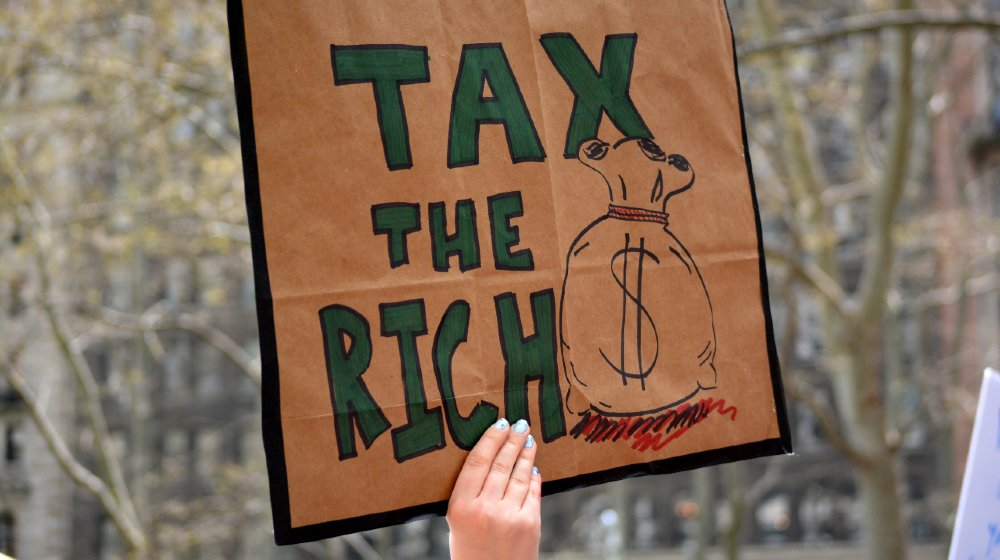 People carrying signs protesting President Trump at the Tax March in Manhattan in 2017 in New York City-Wealth Tax-ss-featured
