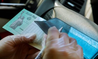 Writing on blank check to with in car with gloves on depositing government stimulus check with gloves on for safety-Stimulus Money-ss-featured