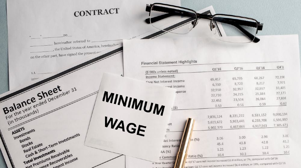 a paper with MINIMUM WAGE text on backgrounwith documents and glasses | Biden To Sign $15 Minimum Wage For Government Contractors | Featured