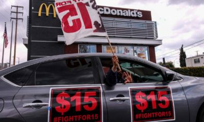 A worker holding a flag in a car during a rally to demand that four McDonald's workers who were fired after raising COVID-19 concerns get back pay and reinstatement | McDonald's To Raise Wages For Corporate Store Workers | Featured