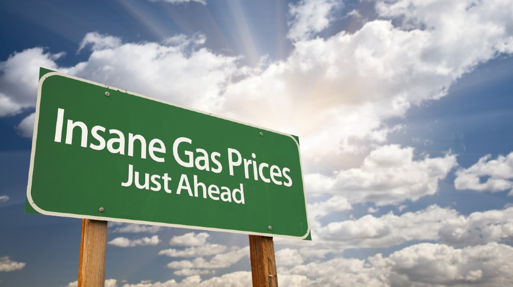 Insane Gas Prices Green Road Sign with Dramatic Clouds, Sun Rays and Sky | Gas Prices Are Now Highest Since 2014 | Featured