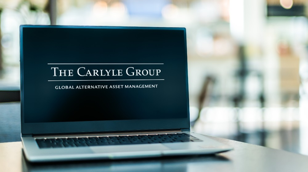 Laptop computer displaying logo of The Carlyle Group, an American multinational private equity, alternative asset management and financial services corporation | BCIM Corp Sells 869 Shares of The Carlyle Group Inc | Featured