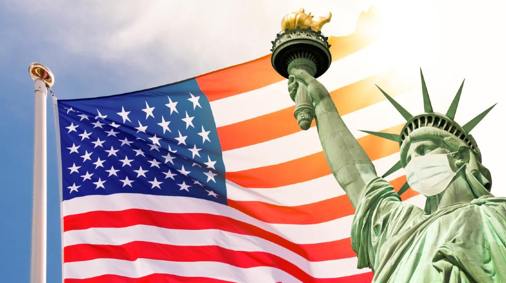 Statue of Liberty wearing a surgical mask, US american flag background | US COVID-19 Cases At Lowest Levels Since June 2020 | Featured