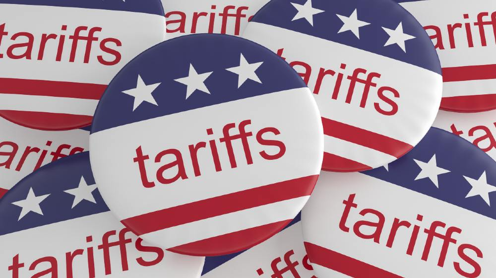 USA Politics News Badges Pile of Tariffs Buttons With US Flag | Businesses Blame Import Tariffs For Inflation | Featured
