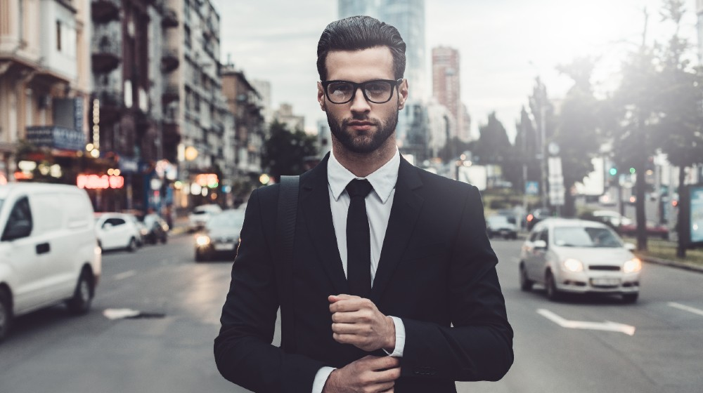 Confident young man in full suit adjusting his sleeve and looking away | How To Be Credible And Confident With Your Choice Of Words | featured