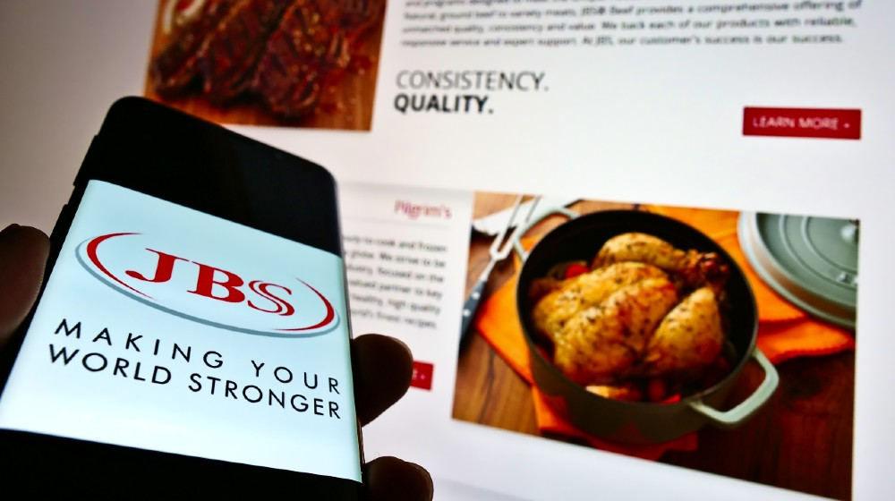Person holding cellphone with logo of Brazilian meet processing company JBS S.A. on display with website | Cyberattack Hits World's Largest Meat Supplier | Featured