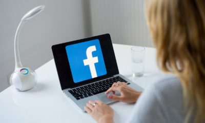 Young woman using laptop with Facebook logo in the screen seeting at the office desk | Facebook Workers Can Work From Home Permanently | featured