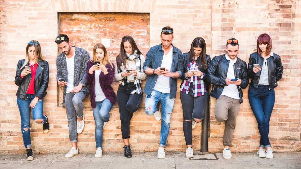 Friends group using smartphone against wall at university college backyard break   Tech firms in new battle for millennials   featured