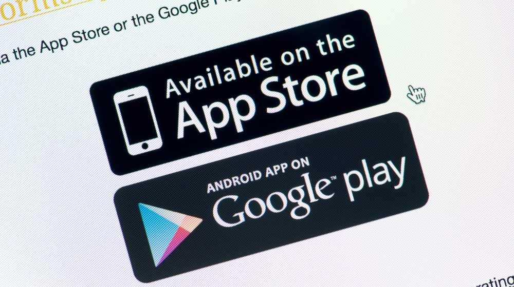 Close-up shot of monitor screen with App Store and Google Play download buttons | South Korea Wants to Ban Apple and Google's Exclusive Stores | featured