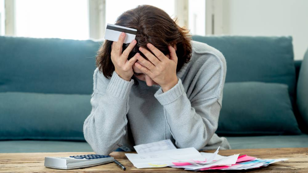 Young attractive woman looking stressed and worried with card payments and home finances   Major Causes of Financial Problems   featured