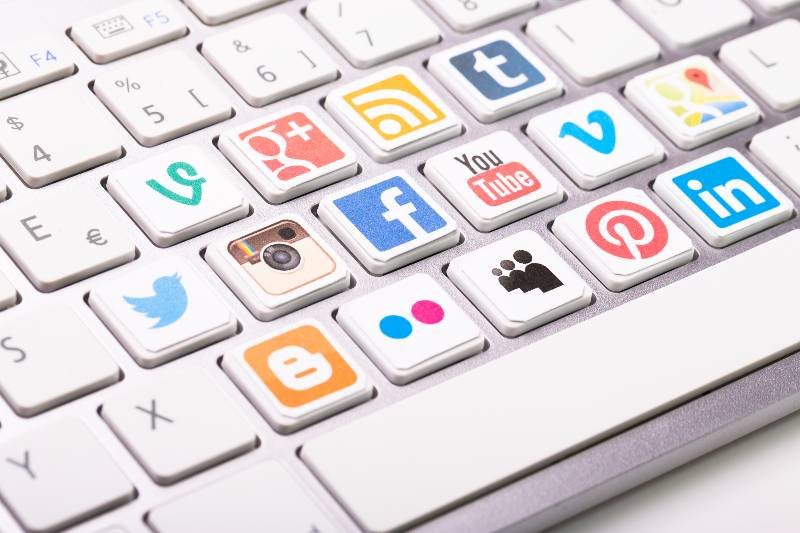 A social media logotype collection printed and placed on modern computer keyboard-Marketing and Social Media