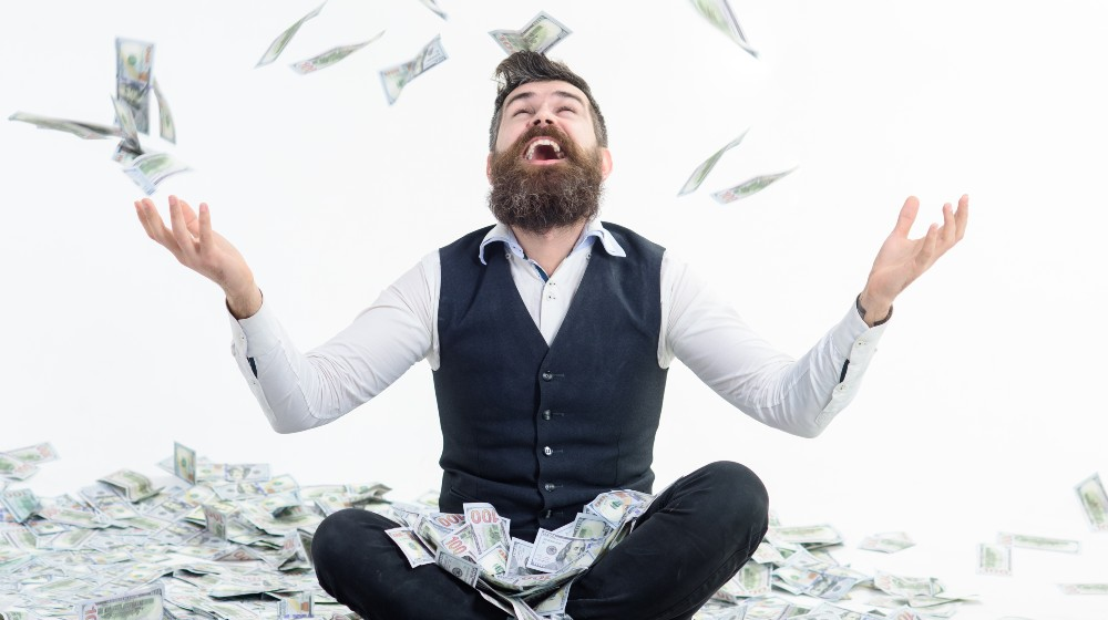 Businessman is happy with his money. Banknotes, cash dollars fly in air | Wealthiest 1% Americans Owe $163 Billion Yearly In Taxes | featured