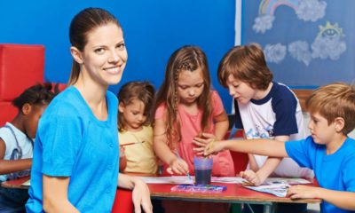 Woman as nursery teacher in kindergarten with group of children painting at table | Child Care Workers Are Leaving Their Jobs For Better Ones | featured