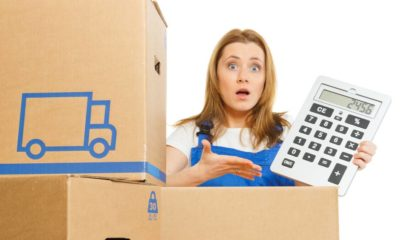 Woman with moving boxes with big calculator | Prepare For Higher Prices of Goods As Freight Costs Rise | featured
