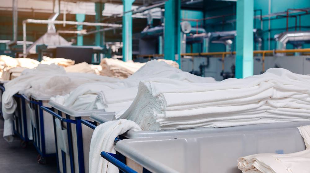 Material on the textile factory. Rolls of industrial cotton fabric for clothing cloth textile manufacture on machine | World's Top 10 Textile Companies | featured
