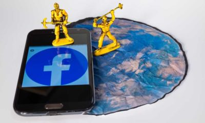 Two toy workers simulate the destruction of the Social Network Facebook on a smartphone | Upcoming Facebook Rebrand Includes Changing Its Name | featured